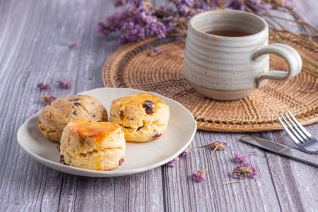 Close-up of traditional British scones and cookie on a plate with a tea cup and flower blurred background. Space for text. Foto de archivo