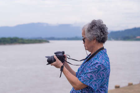 Asian senior woman shooting photo by digital camera at riverside. Elderly woman short white hair, wearing eyeglasses, happy when using a camera. Concept of old people and photography