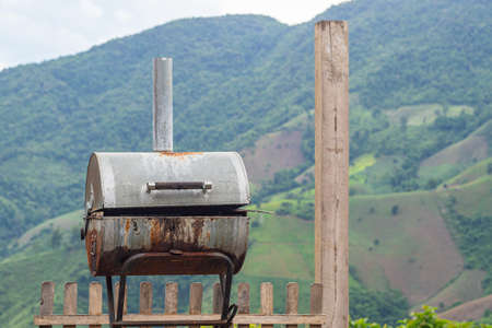 Close-up of old bbq grill stove with mountains background. Space for text.