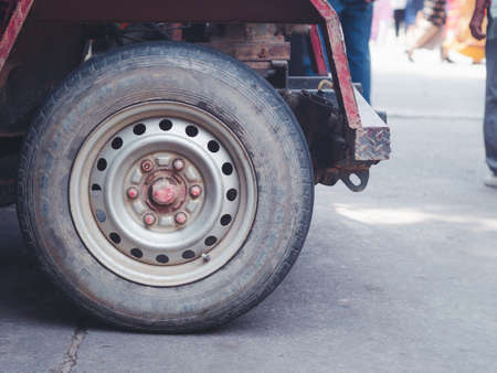 Close-up photo of a car wheel of E-taen Thai tractor. Space for text.
