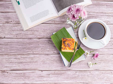 Thai custard cake (or Khanom mo kaeng) on a banana leaf on a white plate and a cup of white coffee with a book and flowers on a wooden table. Egg custard with mung bean flour. Thai dessert is famous.