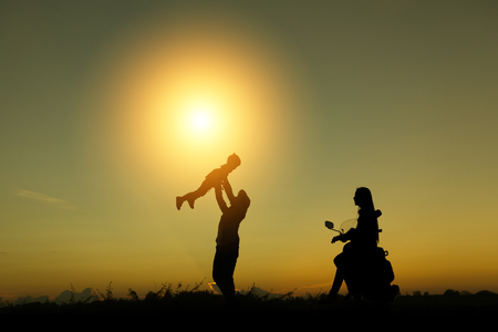 Happy family standing in the park at the sunset time. Banco de Imagens