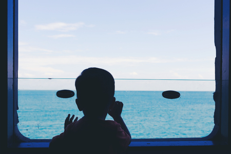 Back view of young boy looking at the sea