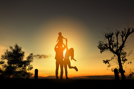 Happy family in the park at the sunset time. Banco de Imagens