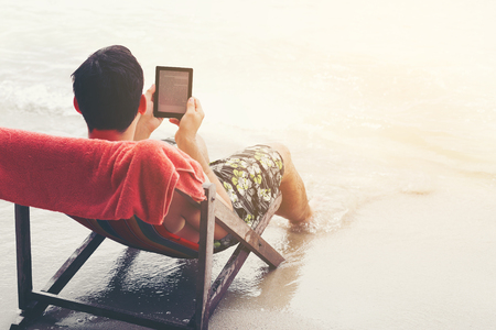 young handsome man reading electronic reader at the beach Banco de Imagens