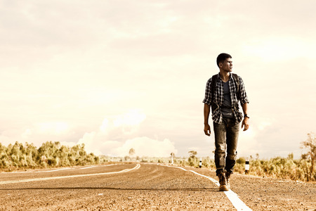 Wanderer or loner walking down an empty road and hot. Stock Photo