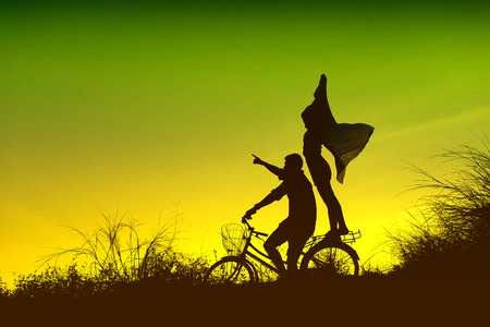 couple on a bicycle at sunset Banco de Imagens