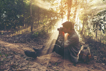 Young Man traveler with retro photo camera walking in forest Fashion Travel Lifestyle outdoor