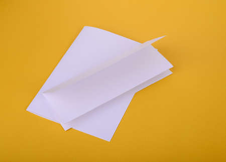 white paper bifold and four-fold brochure mockup on yellow background