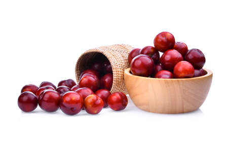 red cherry plum in wooden basket and bowl isolated on white background