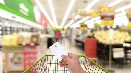 手の男性空クレジット カード、ATM カードでぼやけているスーパー マーケットやデパート、ショッピング カートを押しショッピング概念