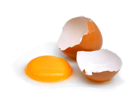 Gebarsten ei met eishell, eierdooier en eiwit dat op witte achtergrond wordt geïsoleerd