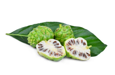 whole and half of noni fruit with green leaf isolated on white background