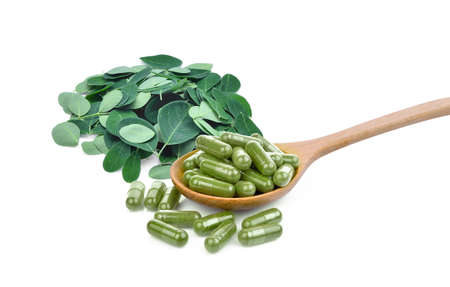 moringa oleifera capsule in wooden spoon with pile of fresh moringa leaves isolated on white background