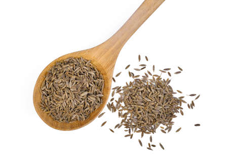 dried cumin seed or caraway in wooden spoon isolated on white background, flat lay, top view