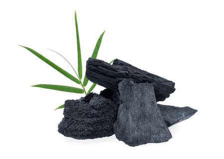 Carbón de leña con hojas de bambú aislado sobre fondo blanco.