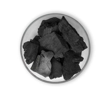 wood charcoal in the glass bowl isolated on white background, flat lay, top view