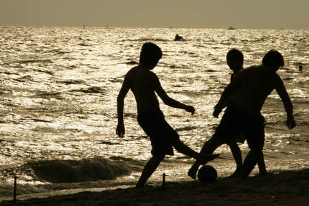 boys playing football beach silhouette lighting photo