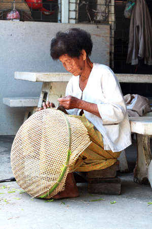 Thai Old woman weaving bamboo baskets photo