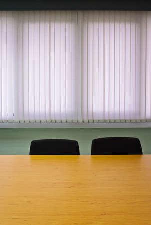 Meeting-Raum mit Stuhl und Tisch gegen Jalousien Standard-Bild