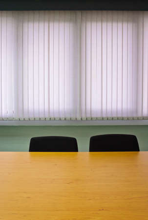 Meeting room with chair and table against window blinds Stockfoto