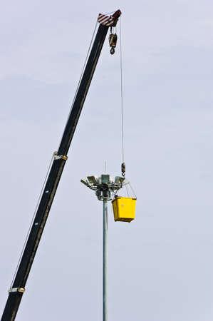 A man in bucket repairs lighting photo