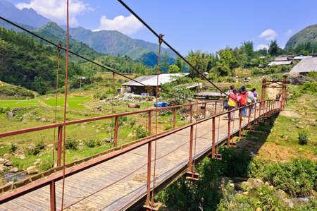 Tourist across a red bridge in Sapa, Vietnam Standard-Bild