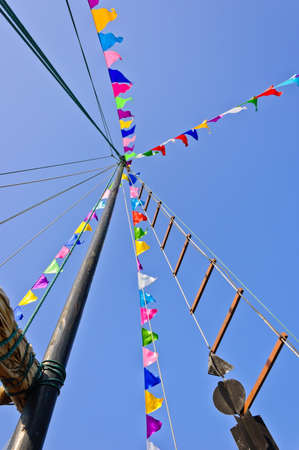 Mast and colorful flags against blue sky photo
