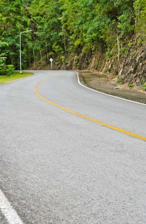 Asphalt curved road in tropical rain forest photo