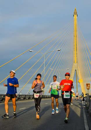 BANGKOK, THAILAND - NOVEMBER 18  Unidentified runner at  Standard Chartered Bangkok Marathon with the Rama 8 bridge in the background  on November 18, 2012 in Bangkok, Thailand