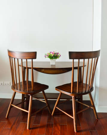 Small dining table with artificial flower pot Stock Photo