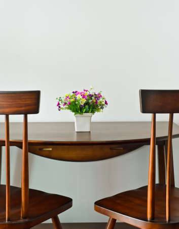 Small dining table with artificial flower pot photo