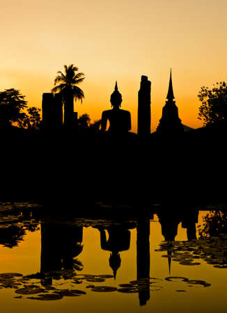 Silhouette of Buddha and pagoda at sunset, Thailand photo