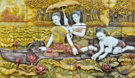 Thai culture stone carving on temple wall photo