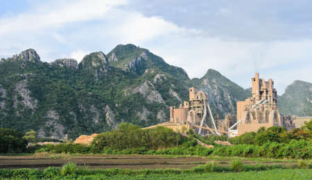 Cement plant with limestone mountain background photo