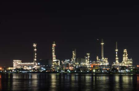 Petrochemical refinery plant illuminated at night photo