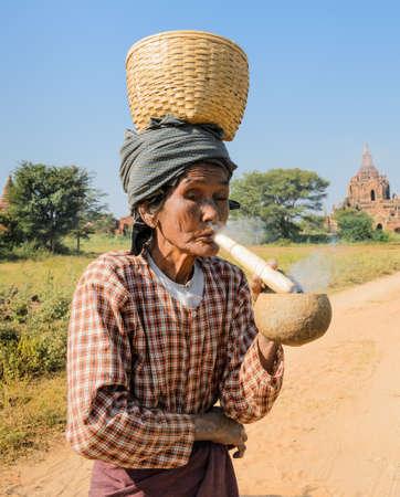 cheroot: Unidentified Burmese woman smoking a cheroot cigar on the road in Bagan, Myanmar Editorial