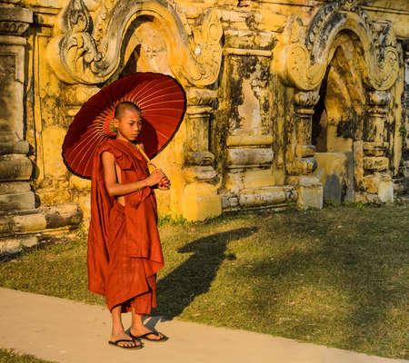 nu: Buddhist novice holding an umbrella at Maha Aungmye Bonzan Monastery in Inwa, Myanmar