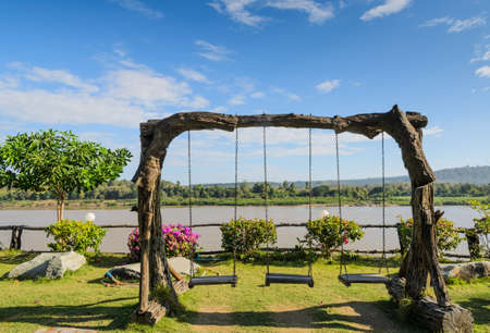 Wooden vintage garden swing on the riverbank photo