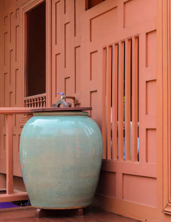 Glazed pottery for water storage on Thai wooden house terrace photo