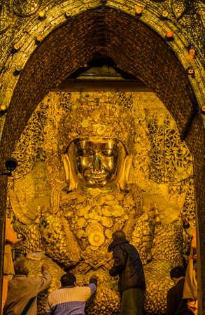 Devotees applying gold leaf to Mahamuni Buddha in Mandalay, Myanmar photo