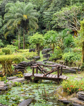 Ornamental garden with foot bridge over a pond photo