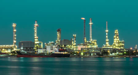 Oil refinery plant illuminated in green background photo