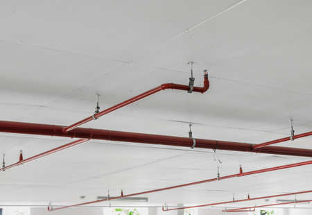 sprinklers: Fire sprinkler and red pipe on white ceiling background