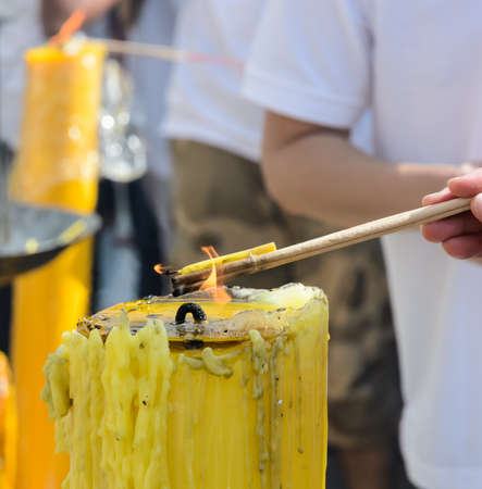 Burning incense sticks on a yellow candle flame photo