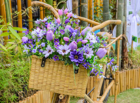 Wooden bicycle with a bucket of colorful flowers photo