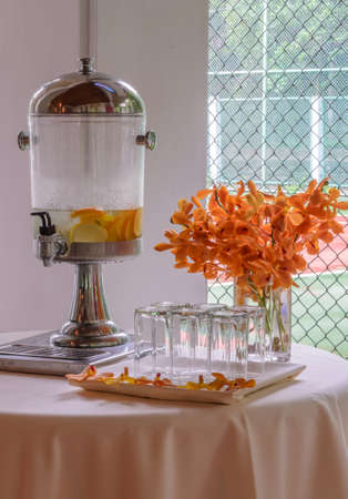 Water dispenser with lemon and orange and glasses on table at reception photo