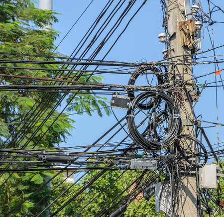Intertwining of many electrical wires on pole photo