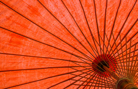 Underside of red fabric umbrella with bamboo frame photo