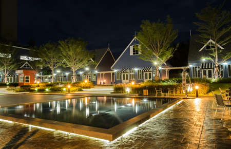 Stunning garden and pool view with Dutch style house illuminated at night Standard-Bild